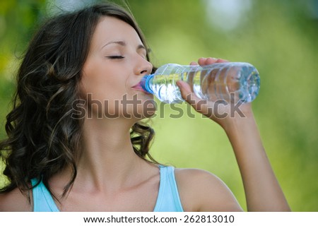 Portrait of young beautiful dark-haired woman wearing blue t-shirt drinking water at summer green park. - stock photo