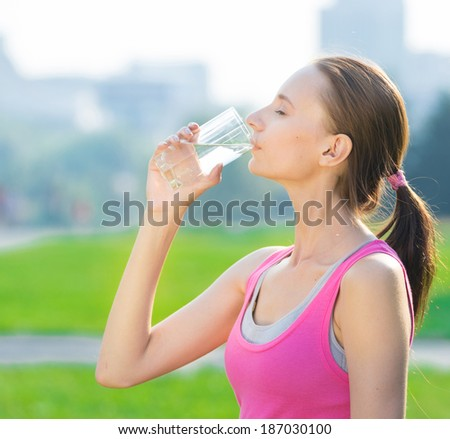 Portrait of young beautiful dark-haired woman wearing pink t-shirt drinking water after sport exercise at summer green park - stock photo