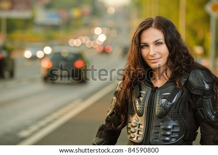 Portrait of young beautiful dark-haired woman wearing protective jacket at road. - stock photo