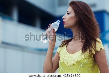 Portrait of young beautiful dark-haired woman wearing trendy knitted vintage t-shirt drinking water on the street. Modern urban background. Copy-space. Close up. Outdoor shot