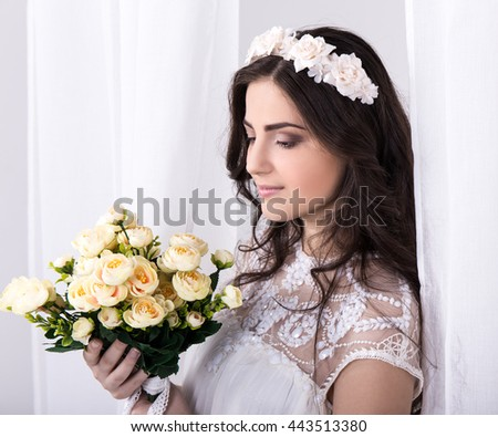 portrait of young beautiful dreaming bride in white dress with flowers near the window