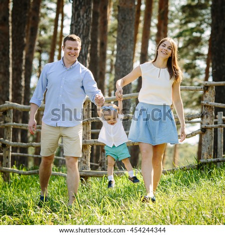 Portrait of young beautiful family of three people mother father daughter walk and play in the park near forest - stock photo