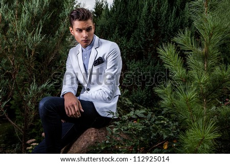 Portrait of young beautiful fashionable man against autumn garden.
