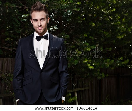 Portrait of young beautiful fashionable man against summer garden. - stock photo