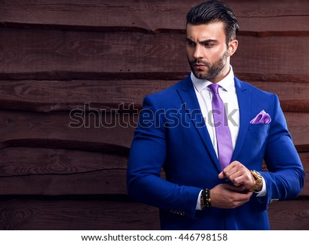 Portrait of young beautiful fashionable man against wooden wall.