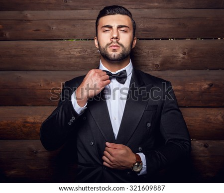 Portrait of young beautiful fashionable man against wooden wall In black suit & bow tie.