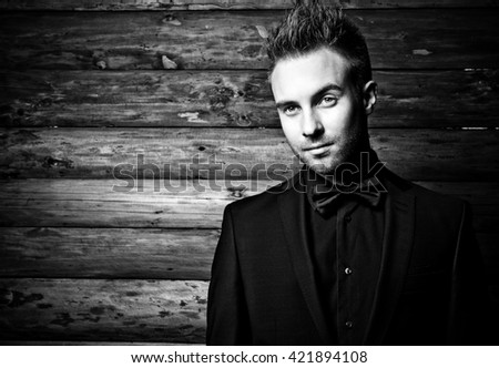 Portrait of young beautiful fashionable man against wooden wall In black suit & bow tie. Black-white fashion photo against wooden background.