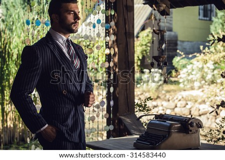 Portrait of young beautiful fashionable man in blue classic suit in summer lodge near old typewriter.