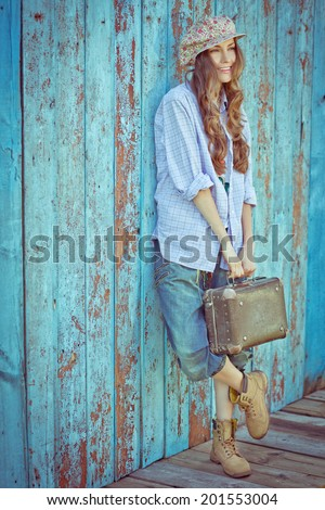 Portrait of young beautiful fashionable woman against wooden wall. Hipster style girl. toned vintage image - stock photo