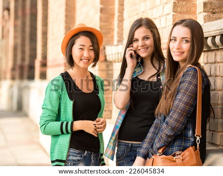 Portrait of young beautiful female students with university building in the background. - stock photo