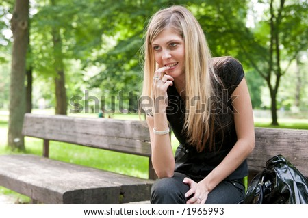Portrait of young beautiful flirting woman siting on bench in park outside - stock photo