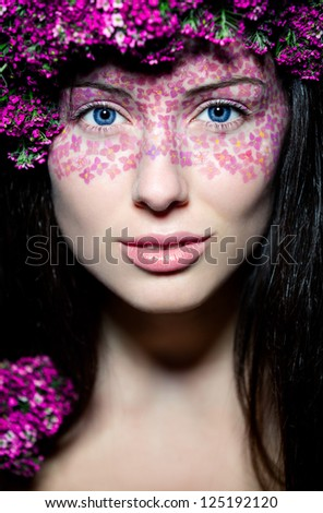 Portrait of young beautiful fresh girl with creative make-up and flowers