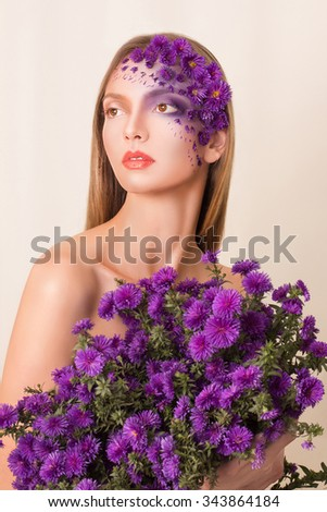 Portrait of young beautiful fresh girl with stylish make-up and purple flowers around her face and hair. - stock photo