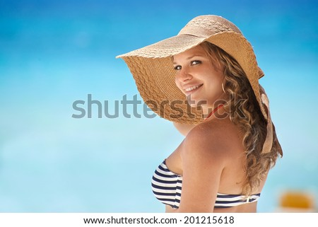 Portrait of young beautiful girl at tropical beach in Cuba for vacations, looking at camera and smiling. Copy space on sea - stock photo