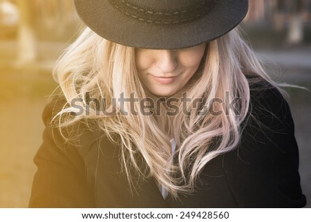 Portrait of young beautiful girl closing hat half of the face - stock photo