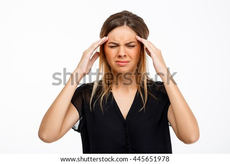 Portrait of young beautiful girl having headache over white background.