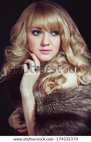 Portrait of young beautiful girl in fur on isolated black background