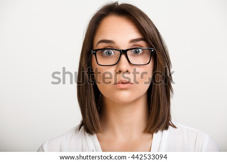 Portrait of young beautiful girl in glasses playing ape over white background.