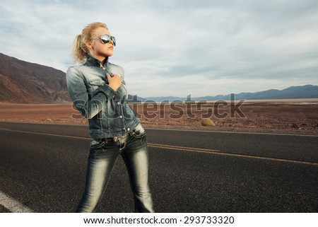 portrait of young beautiful girl in hat and sunglasses in desert  environment  - stock photo