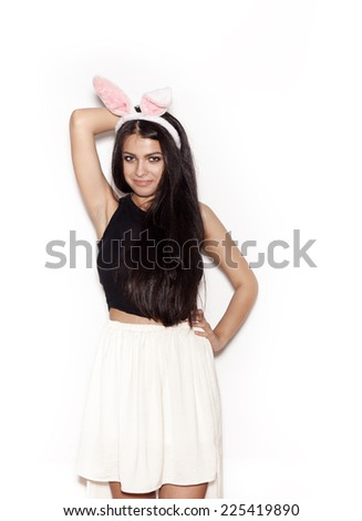 Portrait of young beautiful girl in pink bunny ears. Sweet woman having fun on white background, not isolated