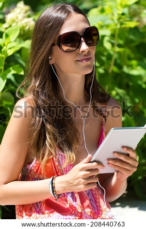 Portrait of young beautiful girl listening to music with digital tablet in the garden.