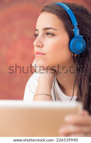 Portrait of young beautiful girl listening to the music - stock photo