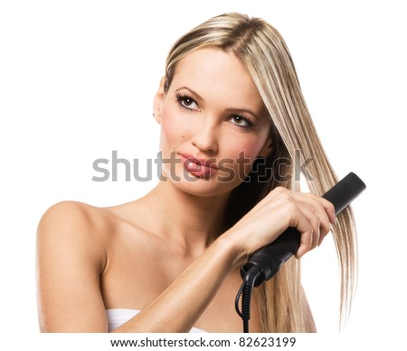 Portrait of young beautiful girl making hairstyle with hair iron