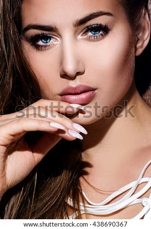 Portrait of young beautiful girl on wooden brown background. Girl with long hair and blue eyes looking at camera. Sexy look.