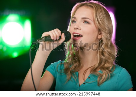 Portrait of young beautiful girl singing. closeup of blond girl holding mic - stock photo