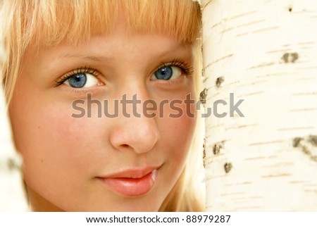 Portrait of young beautiful girl  standing near birch tree in summer - stock photo