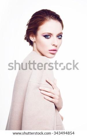 Portrait of young beautiful girl wearing coat. Fashion model. Red hair. Makeup. - stock photo