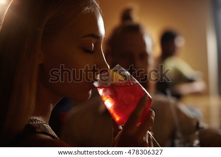 Portrait of young beautiful girl with blond hair holding ice cocktail, closing her eyes, enjoying cold alcohol drink while chilling out with friends in club. People, leisure and lifestyle concept