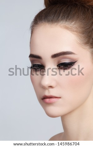 Portrait of young beautiful girl with cat eye make-up - stock photo
