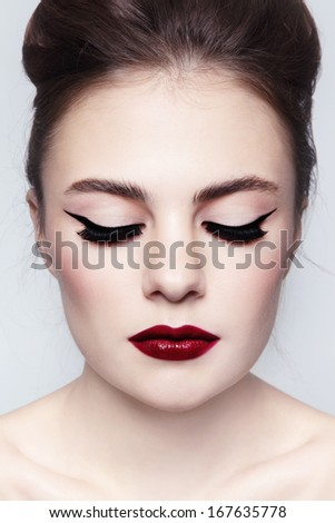 Portrait of young beautiful girl with cat eyes and red lips - stock photo