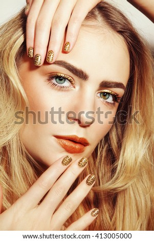 Portrait of young beautiful girl with golden make-up and fancy wild manicure - stock photo