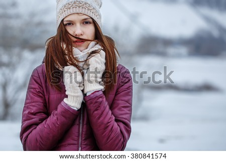 portrait of young beautiful girl with heat scarf and bright jacket with ginger hair freezing and looking to camera on winter windy natural background. Outdoor photo with cold colors - stock photo