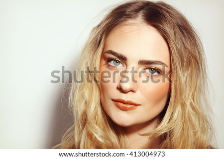 Portrait of young beautiful girl with long messy hair and golden make-up