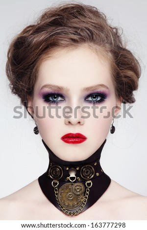 Portrait of young beautiful girl with stylish hairdo and fancy steampunk collar - stock photo