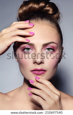 Portrait of young beautiful girl with stylish hairdo, make-up and manicure - stock photo