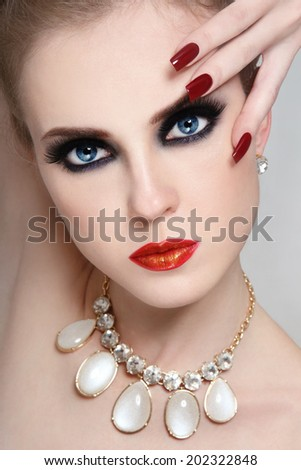 Portrait of young beautiful glamorous woman with smoky eyes and long nails - stock photo