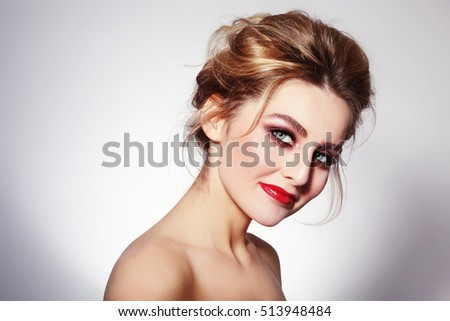 Portrait of young beautiful glamorous woman with stylish make-up and messy hair bun