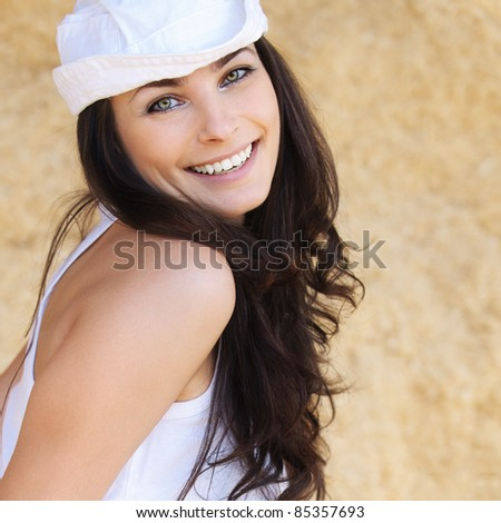 Portrait of young beautiful happy brunette woman wearing white cap, white t-shirt against yellow background.