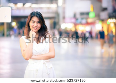 Portrait of young beautiful happy confident Asian woman smiling in city street