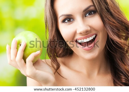 Portrait of young beautiful happy smiling woman with green apple, outdoors - stock photo