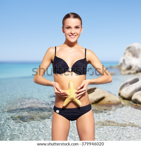 portrait of young beautiful happy woman in black bikini with sea-star  on sea background