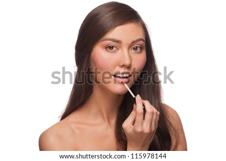 Portrait of young  beautiful healthy woman putting on lip gloss. Isolated on white background - stock photo