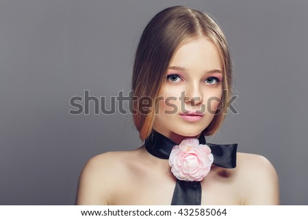 Portrait of young beautiful healthy woman with fancy pink rose on a strip over her neck. Gray background - stock photo