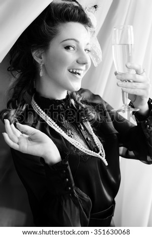 Portrait of young beautiful lady standing in the palace room with champaigne glass over window or door background. Black and white photography