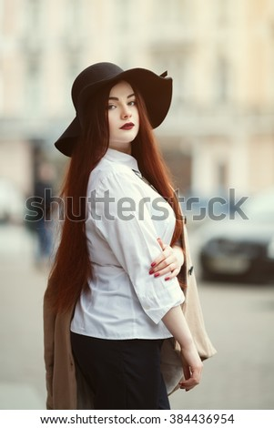 Portrait of young beautiful lady wearing stylish classic clothes posing at street of the old city. Girl looking at camera. Plus size model. Female fashion concept. Close up. Toned - stock photo