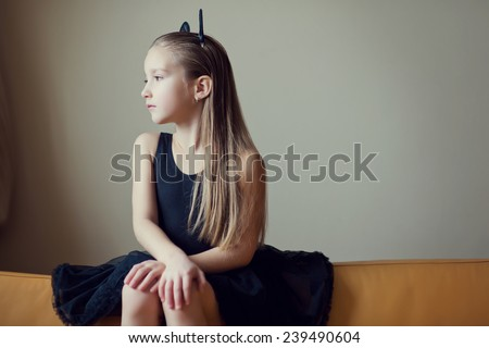Portrait of young beautiful lonely model fashion child girl with long blond hair sad face and fancy toy ears on head in black costume  - stock photo